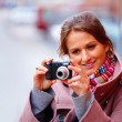 Young happy girl clicking photographs from her digital camera - Stock Photo