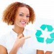 Environmentally friendly woman pointing at recycling symbol - Stock Photo