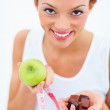 Woman holding an apple and chocolate trying to decide - Stock Photo
