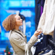 Royalty-Free Stock Photo: Woman selecting from range of jackets in a  showroom