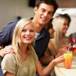 Royalty-Free Stock Photo: Young couple standing at a bar sharing a drink