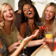 Closeup of laughing young girls holding drinks - Stock Photo