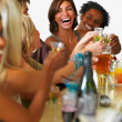 Young friends toasting drinks at a bar - Foto Stock