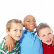 Closeup of young boy with arms around two friends on white backg - Stock Photo