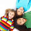 Royalty-Free Stock Photo: Top view portrait of three young girls lying on floor