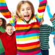 Portrait of group of children jumping with hands raised on white - Stockfoto