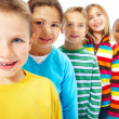Portrait of kids standing in a row one behind the other - Stock Photo