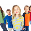 Portrait of group of young children holding hands - Stock Photo