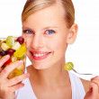 Closeup of smiling young female holding glass full of mixed frui - Stock Photo