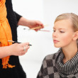 Portrait of young female getting a makeup done by a beautician - Stock Photo