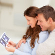 Royalty-Free Stock Photo: Happy young couple holding a sonogram of their unborn child