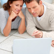 Royalty-Free Stock Photo: Beautiful couple on the floor with a laptop in front