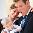 Royalty-Free Stock Photo: Happy business man standing with wife and carrying a baby