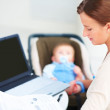 Young business woman working as well as taking care of her baby - Foto Stock