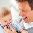Closeup of a happy young father holding a pacifier to his baby's - Stock Photo