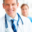 Royalty-Free Stock Photo: Confident young doctor with a female colleague at the back