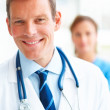 Royalty-Free Stock Photo: Successful young doctor with a female colleague at the back