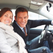 Smiling business man and his pretty wife sitting in a car - Foto Stock