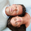 Portrait of young couple lying down besides eachother with their - Stock Photo