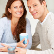 Cute young couple sitting together and drinking coffee - Lizenzfreies Foto