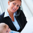 Portrait of beautiful business woman holding a baby and speaking - Stock Photo