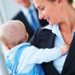 Closeup portrait of young business woman holding a baby and spea - Stock Photo