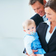 Portrait of business couple holding their baby together - Stock Photo