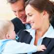 Closeup portrait of business couple holding their baby together - Stock Photo
