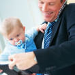 Portrait of smiling young business man holding a cute baby - Stock Photo