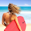 Back view of woman holding surfboard at the beach - Stok fotoğraf