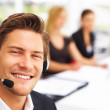 A smiling male secretary/telephone operator in an office environ - Stock Photo