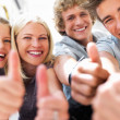Happy boys and girls expressing happiness by showing thumbs up - Stockfoto