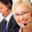 Pretty young blond executive wearing headset - Stock Photo