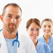 Royalty-Free Stock Photo: Portrait of doctor with two attractive nurses in the back