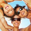 Group of happy young teenagers in circle at beach - Foto Stock