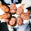 Group of business standing in huddle, low angle view - Stock Photo