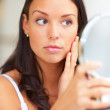 Closeup portrait of young lady holding a mirror - Stock Photo