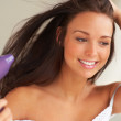 Beautiful smiling woman drying her hair with a blow dryer. - Foto de Stock
