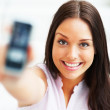 Gorgeous woman showing her cellphone and smiling at camera - Stock Photo