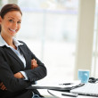 Businesswoman in black suit sitting in office and looking at cam - Stock Photo