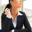 Young beautiful businesswoman in black suit sitting in the offic - Stock Photo