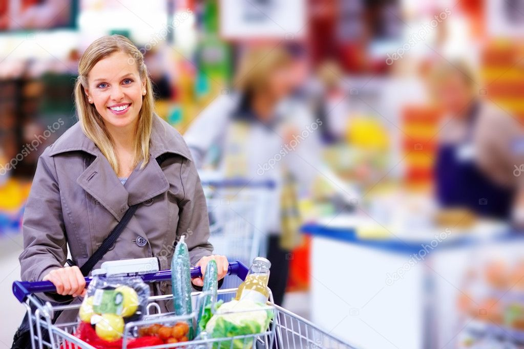 Beautiful young woman standing with a trolley at a supermarket — Stock Photo #3292067