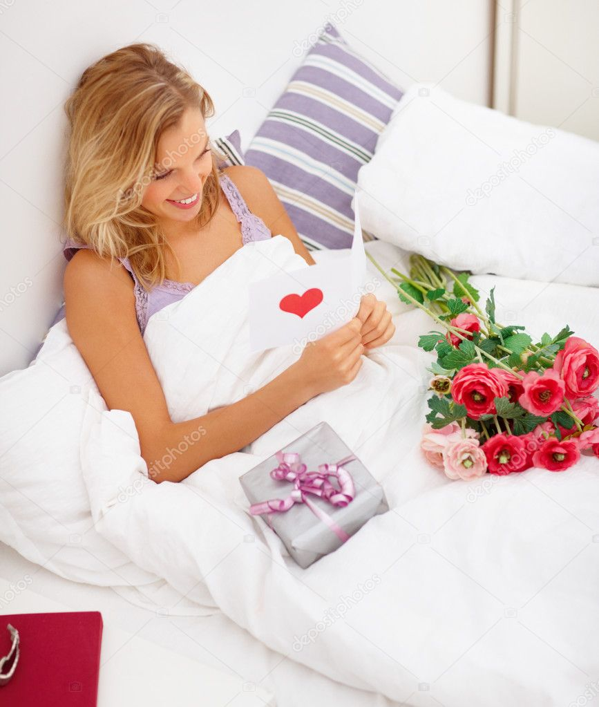 Young happy smiling woman with gifts at bedroom reading a card — Lizenzfreies Foto #3292088