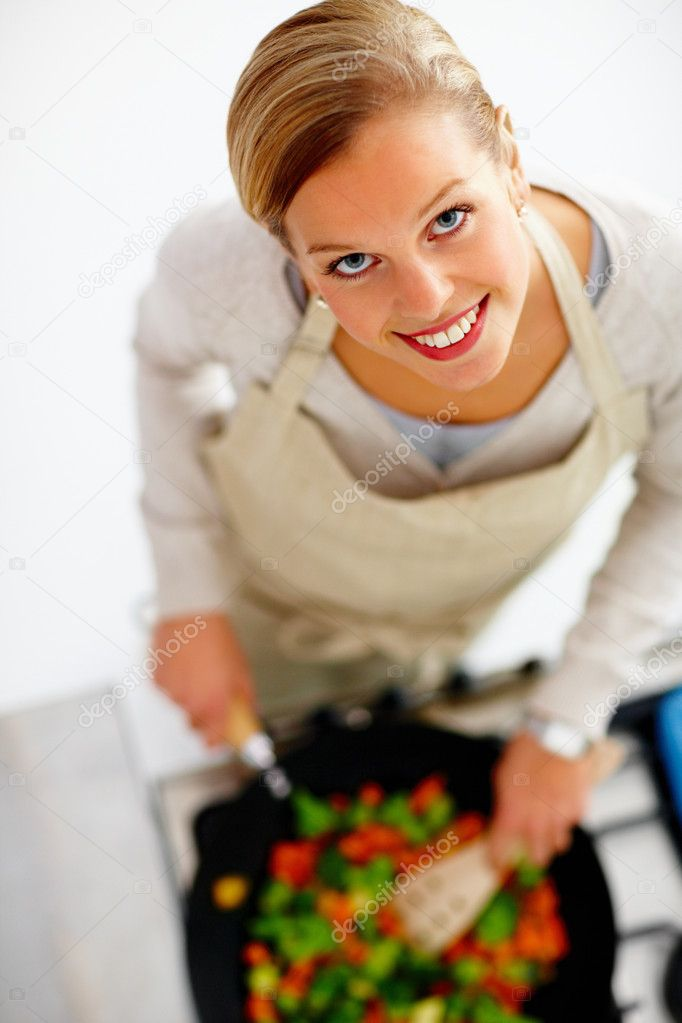 Top view of a young beautiful woman cooking food in kitchen — Stock Photo #3292104