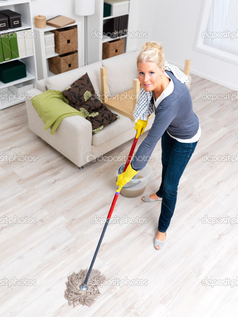 Portrait of a hot young lady in cleaning gear mopping a living room floor  Stock Photo #3292229