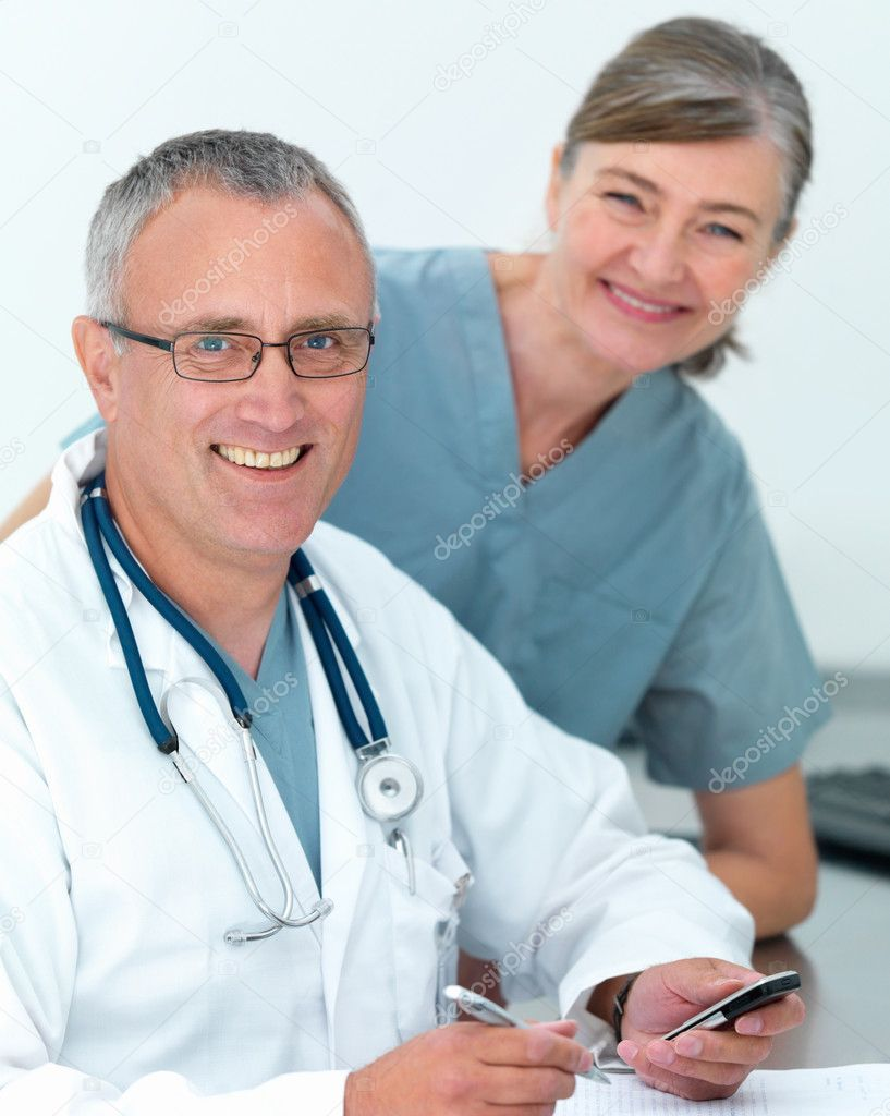Happy Mature doctor and nurse ready to help you — Lizenzfreies Foto #3292415