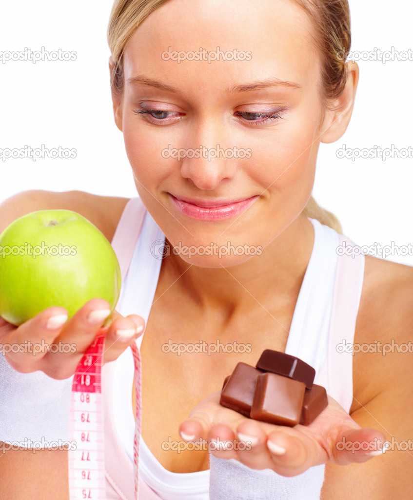 Young woman comparing apple with chocolates over white background  Stock Photo #3294218