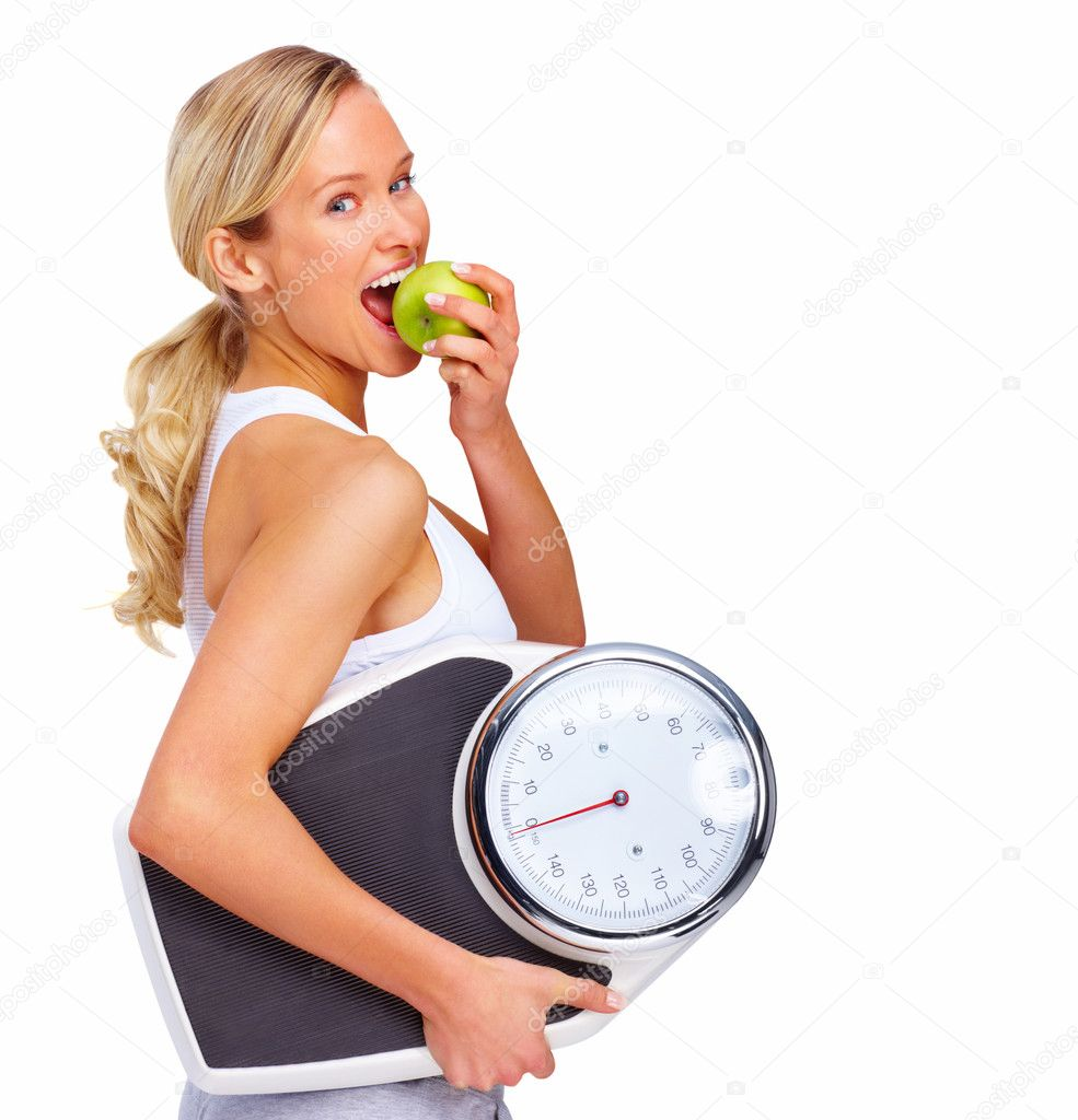 Young woman eating apple and carrying a weight scale over white background  Stock Photo #3294303