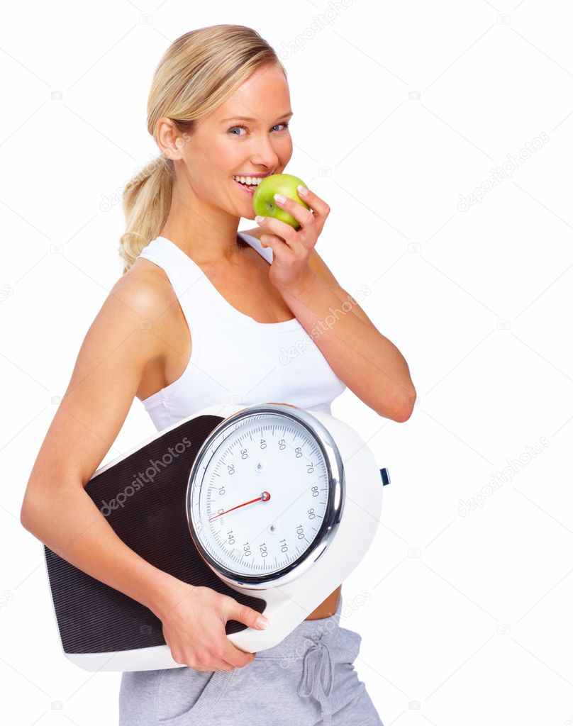 Young healthy woman eating apple and carrying a weight scale over white background — Stok fotoğraf #3294305