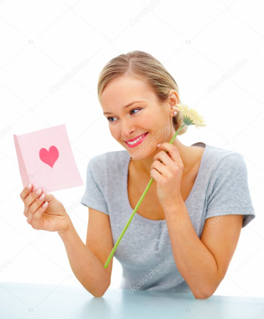 Portrait of a young woman reading greeting card and holding a flower over white background  Stock Photo #3294413